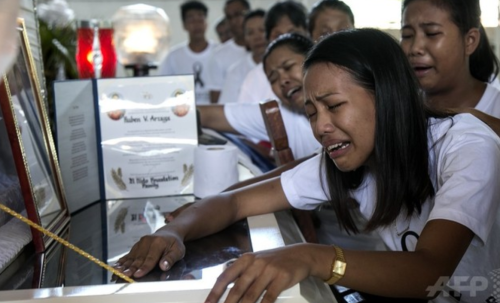 フィリピン・パラワン島のエルニドで、殺害された環境保護団体パラワンNGOネットワーク・インコーポレーテッド(PNNI)のメンバー、ルベン・アルザガさんのひつぎにすがって泣く、アルザガさんの娘