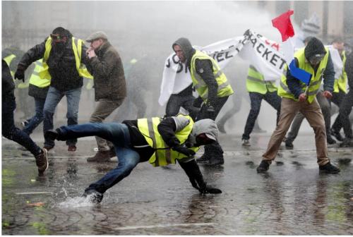 警官の催涙ガスに逃げ惑うデモ隊