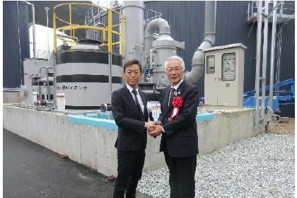 発電設備の前で握手する岡田吉充トーホーグループ社長㊧と広瀬栄・養父市長㊨