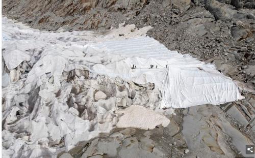 氷河を防水布で覆う作業。手作業で布を広げていく。ローヌ氷河で。