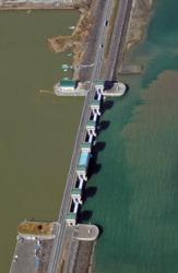 諫早湾干拓事業で造られた潮受け堤防を境に、調整池と有明海側の水の色は違う。調整池(左)は茶色くにごっている=長崎県諫早市で2011年2月15日、本社ヘリから野田武撮影