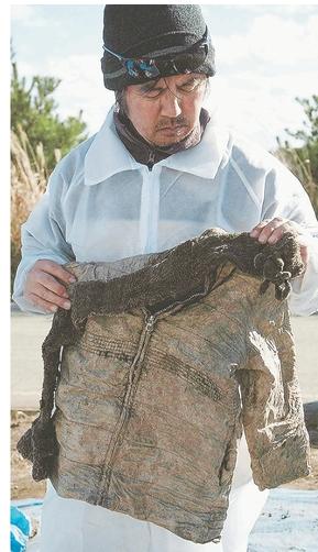 遺骨とともに見つかった汐凪さんのマフラーと上着を手にする父紀夫さん=11日、福島県大熊町(写真家・岩波友紀氏撮影)