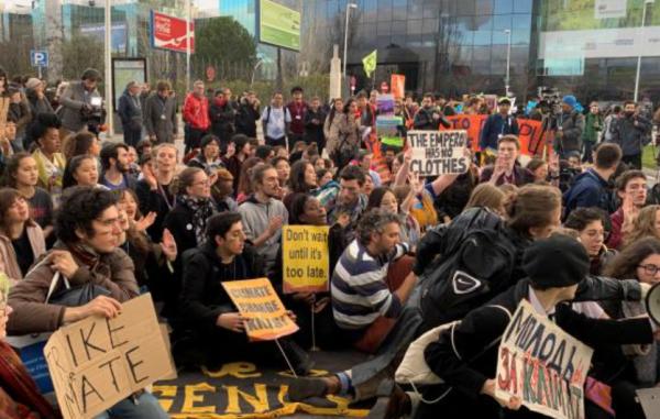 COPの会場の外では、若者たちが抗議の座り込み