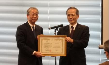 優秀賞の表彰状を掲げる田中英隆取締役専務執行役員(左)