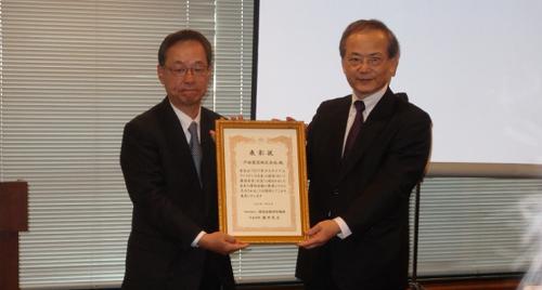 2017年サステナブルファイナンス大賞の表彰状を掲げる戸田建設専務執行役員の鞠谷祐士氏(左)