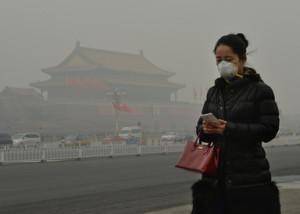 スモッグが垂れ込める北京(Beijing)市内の天安門広場(Tiananmen Square)近くをマスク姿で歩く女性(2014年2月26日撮影、資料写真)。(