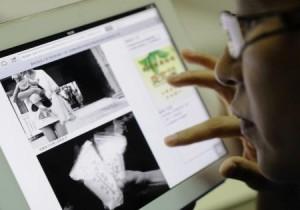 インターネットで、母乳が闇で売買されていることを報じるニュースを見る女性=18日、北京(共同)