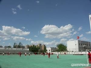 母校の高校のグラウンド(北京市内、2013年4月撮影)。青空が広がる日もあります。後ろには高層マンションがそびえる。