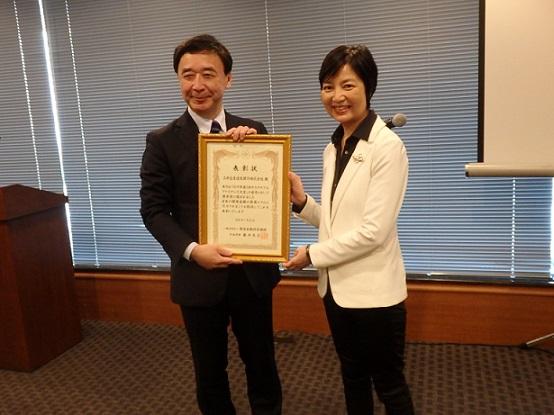 表彰状を受け取る金井氏㊧、㊨は審査委員長の佐藤泉弁護士