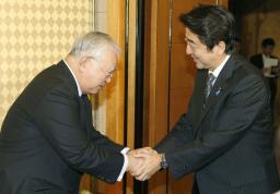 政策懇談会で自民党の安倍総裁(右)を出迎え、握手する経団連の米倉会長=9日午前、東京都内のホテル