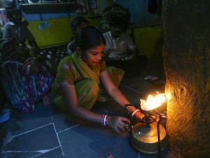 小さな家の中で料理をする女性。インド、ムンバイで。