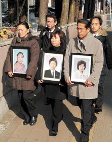 津波で犠牲になった行員らの遺影を抱いて仙台地裁に入る家族ら=25日午前9時30分ごろ、仙台市青葉区