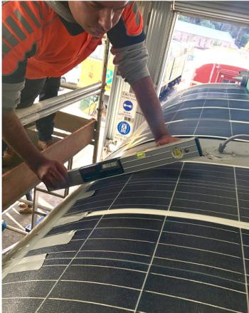 車両の屋根に太陽光パネルを張り付ける様子