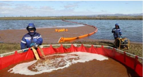 川に流出した軽油の回収作業を続ける作業員