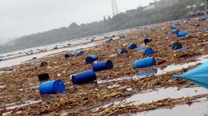 洪水後の川に浮かぶ化学薬品の容器