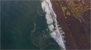 ドローンで上空から撮影した海岸線漂う白灰色の油膜の帯