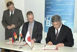 基本合意書に調印する遠藤村長(右)とラウシェン氏。後方はフォークツベルガー大臣