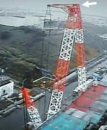 中央付近(矢印)でアームが折れた福島第1原発3号機脇の大型クレーン。アームの先端部が画面右側方向の地面に向かって落下し、くの字になった=5日(東京電力提供)