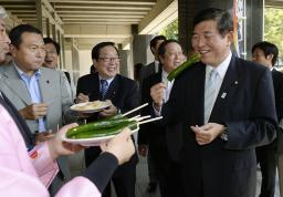 福島県産農産物の産直販売会でキュウリを食べる自民党の石破茂幹事長=27日午前、東京・永田町