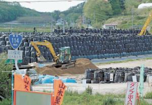 ピラミッド状に積まれた除染廃棄物の山。避難住民は、除染の進み具合を複雑な思いで見詰めている=福島県川俣町山木屋地区