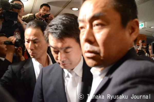 警察のSPに両脇を固められ記者会見場に入る橋下大阪市長。うつ向き険しい表情だった。法廷に引きずり出されるような気分なのだろうか。=27日、正午 写真:田中龍作=