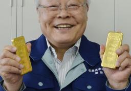 石巻魚市場に匿名で届いた金の延べ板を手にする須能邦雄社長=14日午前、宮城県石巻市