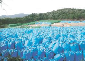 除染廃棄物を詰めた青い袋が山積みになっている仮置き場。奥では積み重ねた袋が緑のシートで覆われている=18日、福島県川内村