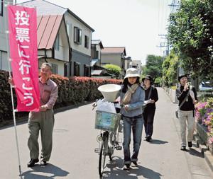 投票を呼びかける「小平都市計画道路に住民の意思を反映させる会」メンバーら。自転車の前かごには「5月26日住民投票に行きましょう」と書かれた会手作りのプレート=小平市で