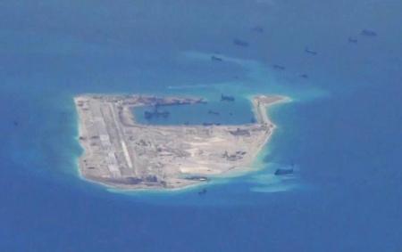 6月25日、中国が南シナ海の南沙諸島で進める岩礁の埋め立て工事。海洋環境の専門家の間では、東南アジアで最も重要なサンゴ礁生態系の1つに深刻なダメージを与えていると危惧する声が高まっている。写真は永暑礁で、米海軍の提供映像から(2015年 ロイター)