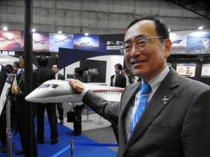 MRJの模型を前に笑顔を見せる三菱航空機の江川豪雄社長=名古屋市港区の「ポートメッセなごや」で2012年10月9日、高橋昌紀撮影