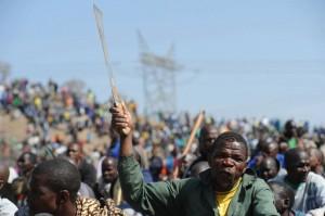 南アフリカ・マリカナ(Marikana)の鉱山で、なたを振り上げる座り込みに参加したストライキ中の労働者(2012年8月16日撮影)。 ©AFP=時事