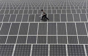 太陽光パネルの上を歩く作業員(2012年5月18日、中国新疆ウイグル自治区アクス)