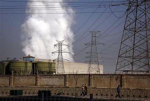 石炭火力発電所の煙突の前を歩く人々(12年1月12日、中国北京)