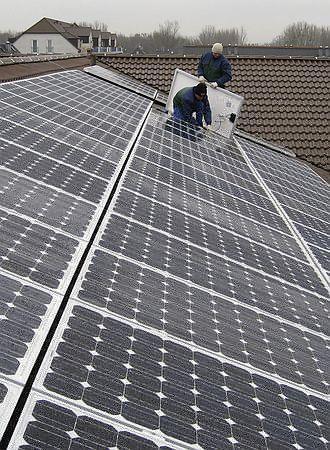農場の屋根に太陽光発電装置を取り付ける作業員(2012年3月21日、独バイエルン州ランツフート近郊)