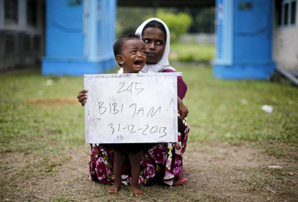 """A Rohingya migrant mother (R) and her child, who recently arrived in Indonesia by boat, hold a placard while posing for photographs for immigration identification purposes inside a temporary compound for refugees in Aceh Timur regency, Indonesia's Aceh Province May 22, 2015.  Myanmar's military commander-in-chief said some """"boat people"""" landing in Malaysia and Indonesia this month are likely pretending to be Rohingya Muslims to receive U.N. aid and that many had fled neighbouring Bangladesh, state media reported on Friday. REUTERS/Beawiharta - RTX1E2GB"""