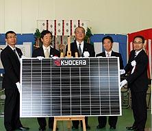 ソーラーパネルを囲み、発電施設の起工を喜ぶ関係者