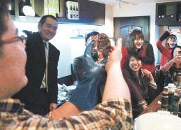 東京・新橋であった消費者との交流会でカキの殻むきを実演する阿部さん(左